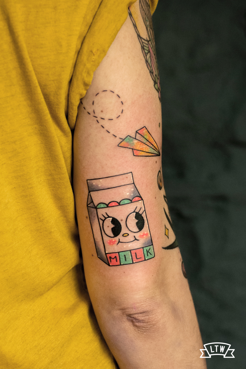 Milk brick and paper plane tattoo done by Numi and her particular style
