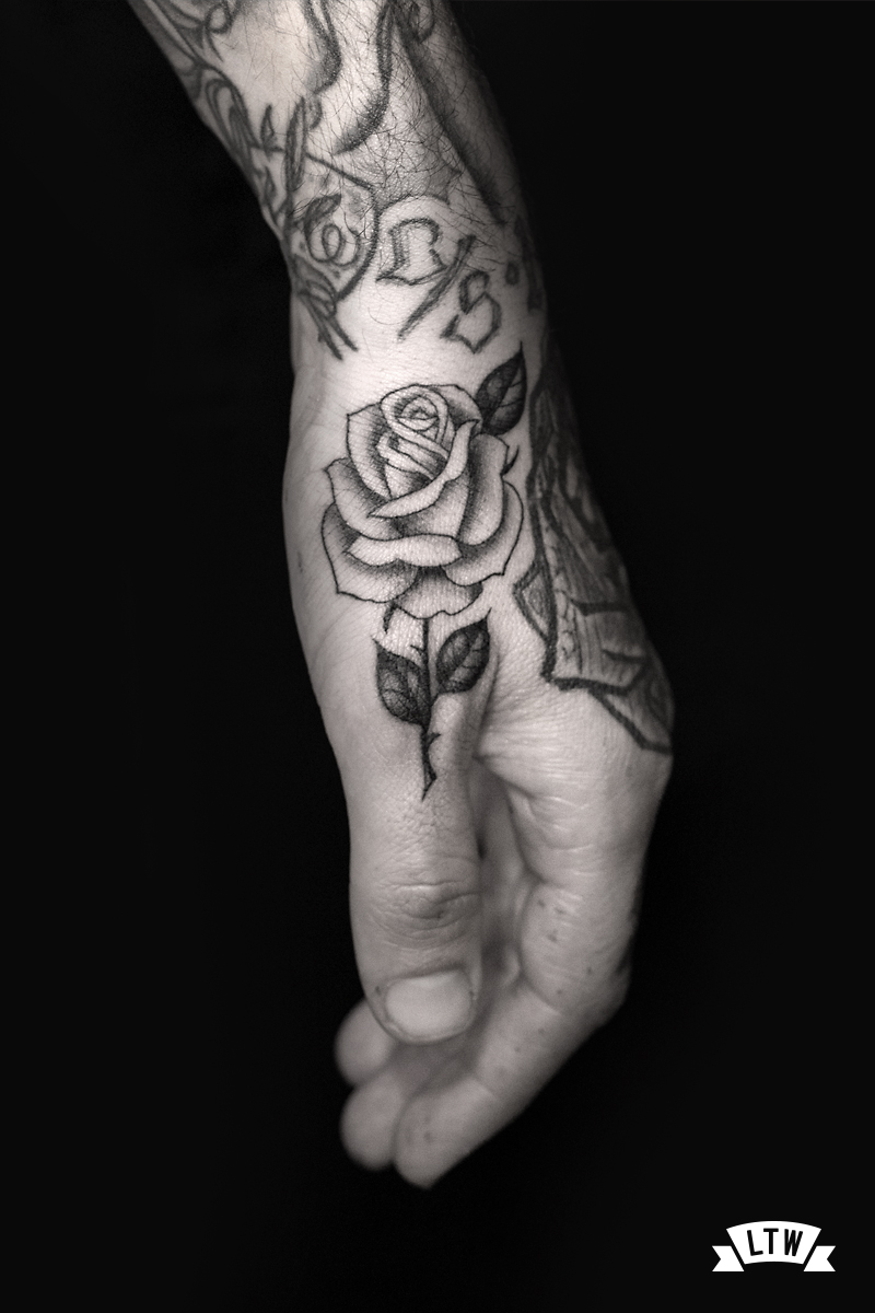 Rose on a finger tattooed by Alexis