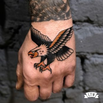 Eagle tattooed on a hand by Dennis